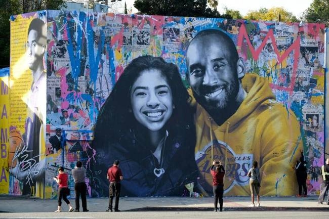 People stop to take pictures in front of the new mural by French artist Mr. Brainwash picturing Kobe Bryant and his daughter Gigi in Los Angeles on Jan. 31, 2020. — AFP