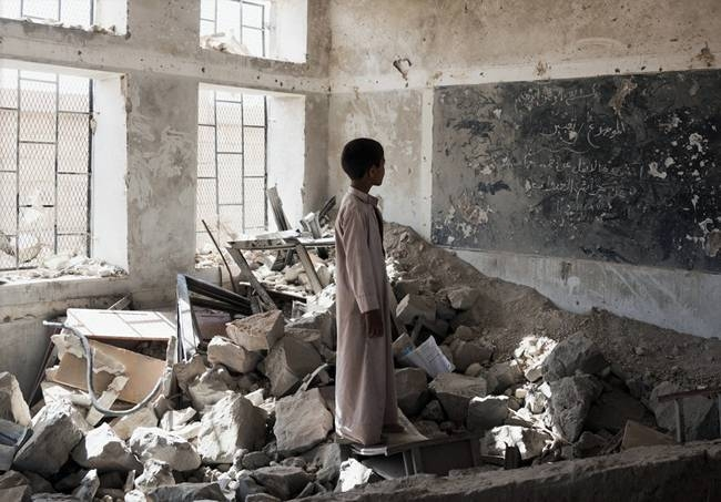 File photo shows a student standing in the ruins of one of his former classrooms, which was destroyed in June 2015, at the Aal Okab school in Saada, Yemen.
