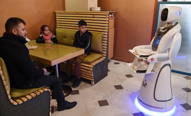 Afghanistan's first-ever robot waitress glides up to a table of curious diners in central Kabul and presents them with a plate of French fries. — AFP