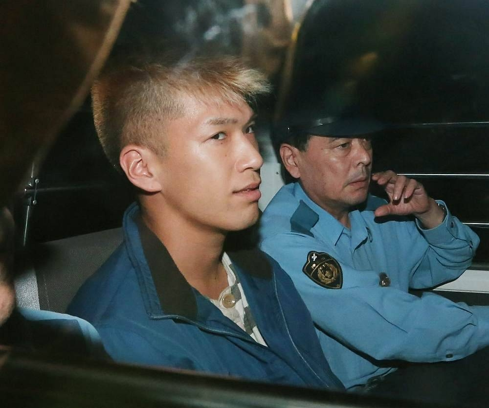 Murder suspect Satoshi Uematsu, left, as he returns to the Tsukui police station in Sagamihara, Kanagawa prefecture, Japan, in this July 27, 2016 file photo. — AFP