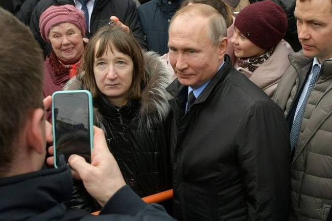 The woman seen here with President Vladimir Putin asked the Russian leader about cost of living. — AFP