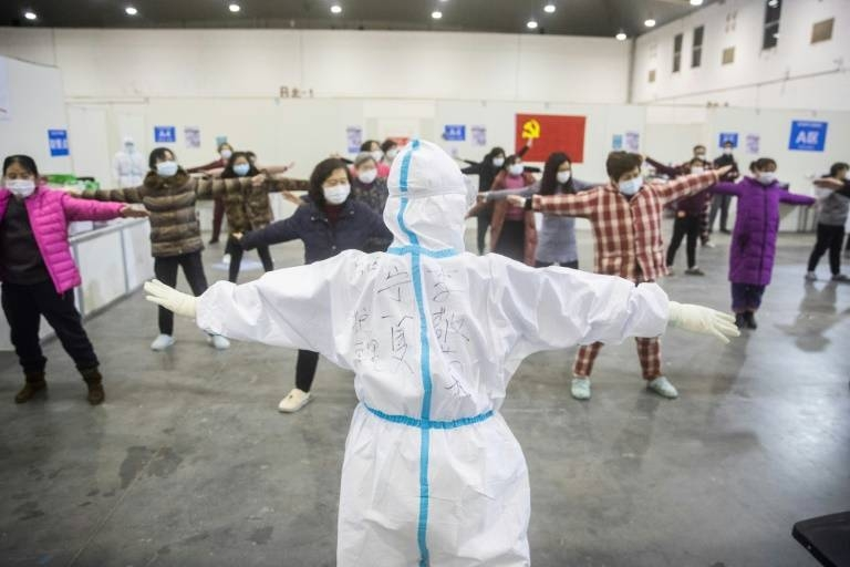 Medical staff in Wuhan, the centre of China's coronavirus outbreak, lead patients in group exercises at a hospital. — AFP
