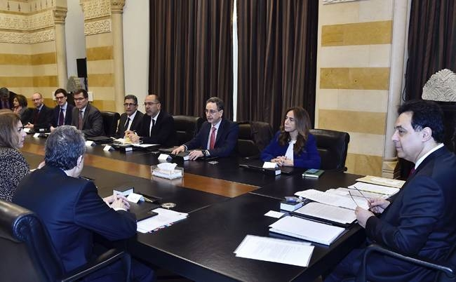 In this photo released by the Lebanese government, Lebanese Prime Minister Hassan Diab, right, meets with delegation from the International Monetary Fund at the Government House in Beirut, Lebanon, on Thursday.