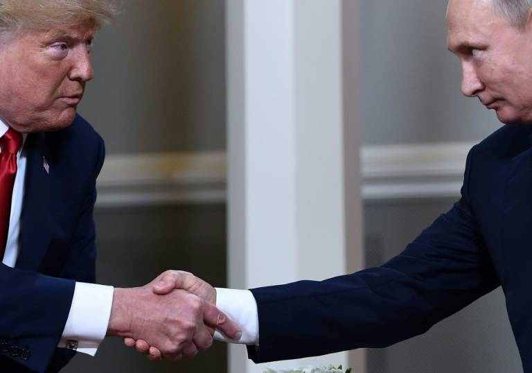 US President Donald Trump and Russian President Vladimir Putin shake hands ahead of a meeting in Helsinki in July 2018. — AFP