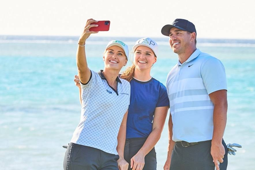 Amy Boulden and Rachel Drummond pose with Brooks Koepka. — Courtesy photos