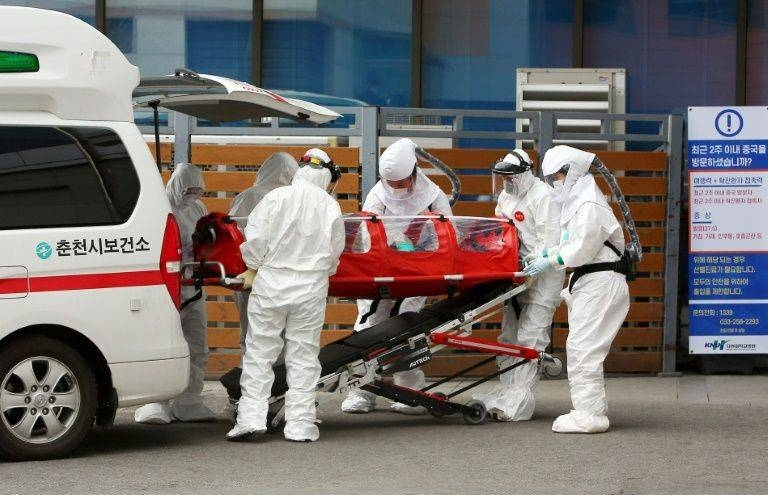 Medics carry a patient infected with coronavirus to hospital in Chuncheon, South Korea. — AFP
