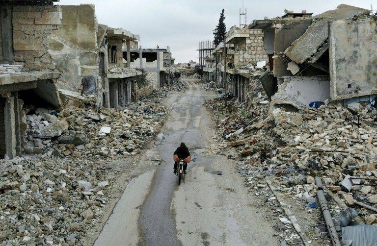 A man rides a motorbike through the almost-deserted town of Kafranbel on Feb. 15, just days before its capture by the regime. — Archives