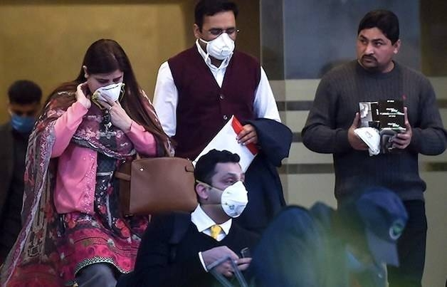 People wearing protective facemasks walk out from a Pakistan-based Chinese company in Islamabad on Jan. 30, 2020, after instructions from Pakistani authorities to take preventive measures against the coronavirus. —  AFP