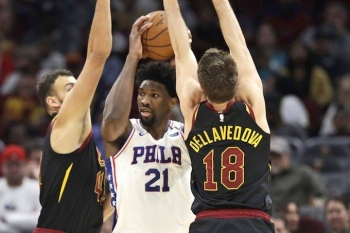 Philadelphia 76ers' Joel Embiid, center, squeezes between Cleveland Cavaliers' Ante Zizic, left and Matthew Dellavedova in the first half of an NBA basketball game, Wednesday in Cleveland.