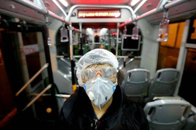 A worker cleans a bus in the Iranian capital Tehran as part of efforts to prevent the spread of coronavirus. — AFP