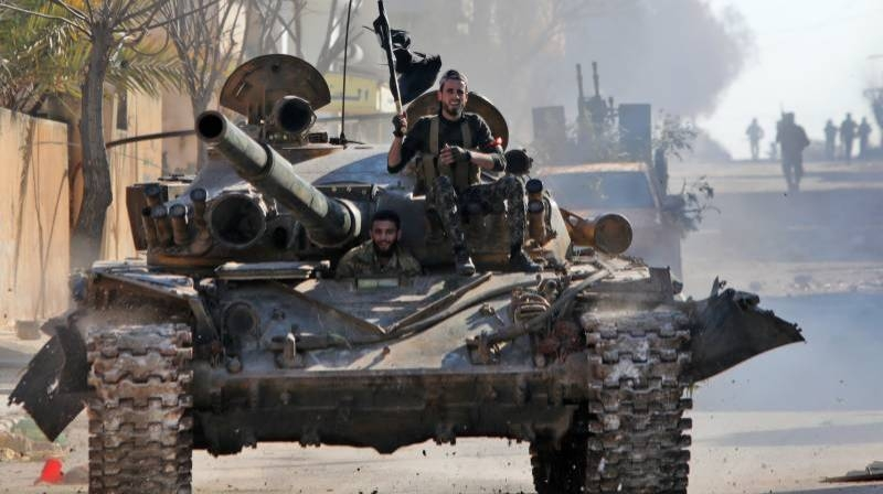 Turkey-backed Syrian fighters ride a tank in the town of Saraqib in the eastern part of the Idlib province in Syria. — AFP