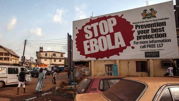 People pass a banner reading 'STOP EBOLA' forming part of Sierra Leone's Ebola free campaign in the city of Freetown, Sierra Leone, in this file photo.