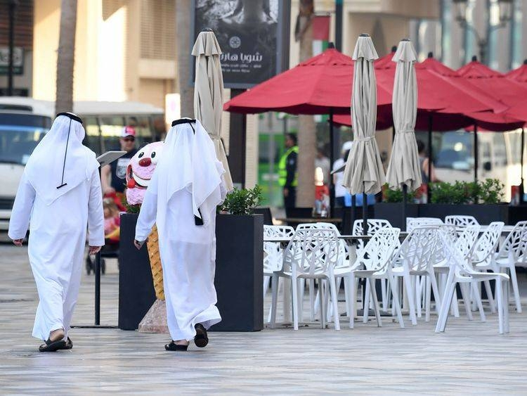 Emirati men walk along the empty beachside boulevard of Jumeirah Beach Residence in this file picture. — Courtesy photo