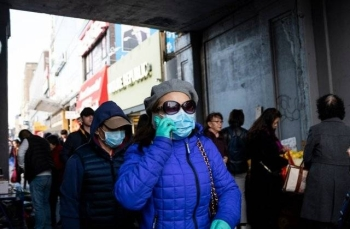 People wear face masks as they walk down a street in New York City in this March 2, 2020 file picture. — Courtesy photo