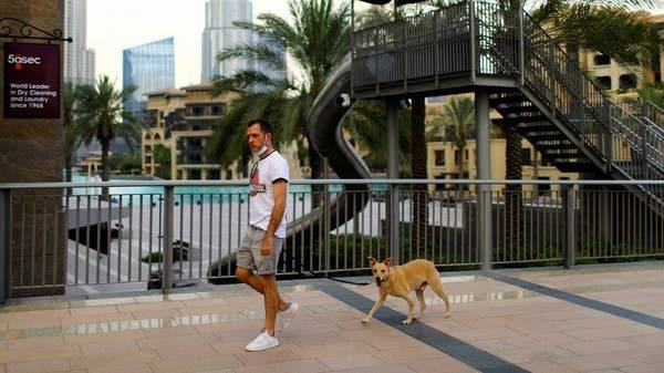 A man with a protective face mask, walks his dog, in downtown Dubai. -- Courtesy photo