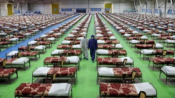 People in protective clothing walk past rows of beds at a temporary 2,000-bed hospital for COVID-19 coronavirus patients set up by the Iranian army at the international exhibition center in northern Tehran. -- Courtesy photo