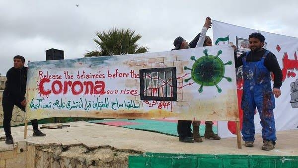 The Syrian artist Aziz Asmar helds up a painted banner asking for the release of detainees in Syria amid the threat of coronavirus. -- Courtesy photos