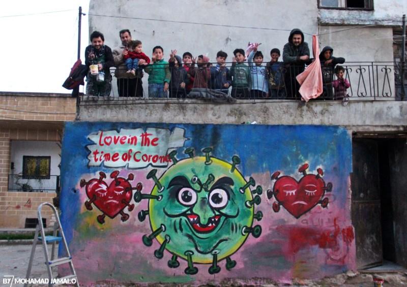 Aziz Asmar with children in Idlid above one of his coronavirus murals.