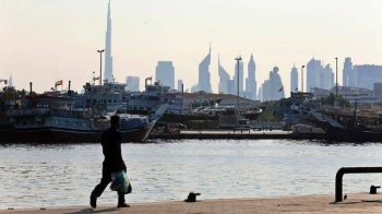 A man walks at Dubai creek where ships are loaded with goods. -- Courtesy photo