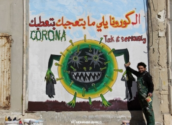 Aziz Asmar with a coronavirus mural in Idlib.