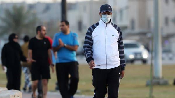 A man wearing a protective face mask walks in Saudi Arabia. Behind him, men are seen without masks. -- File photo