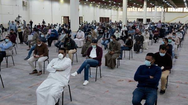 Expatriates wait for mandatory coronavirus testing in a makeshift testing center in Mishref, Kuwait. -- File photo