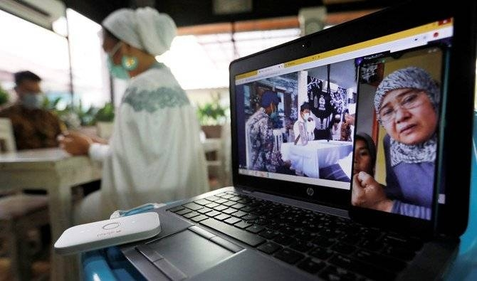 Family members are seen on a computer screen showing video conference as the bride prays in the background, during a wedding ceremony which streamed online from Bahrain amid the spread of coronavirus, in Tangerang, on the outskirts of Jakarta. -- Courtesy photo