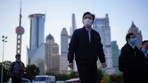 People wear protective face masks at the Lujiazui financial district in Shanghai, China. -- File photo