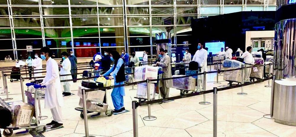 Pakistanis wait to complete departure procedures in Riyadh as they are repatriated to Islamabad by a PIA flight.