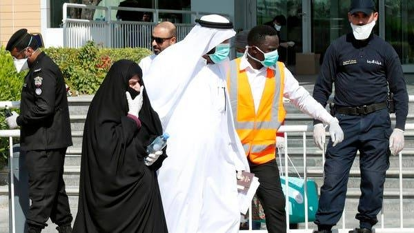 Qatari police stand outside a hotel in Doha as a medical worker walks alongside people wearing protective masks over fears of coronavirus in this file picture. — Courtesy photo