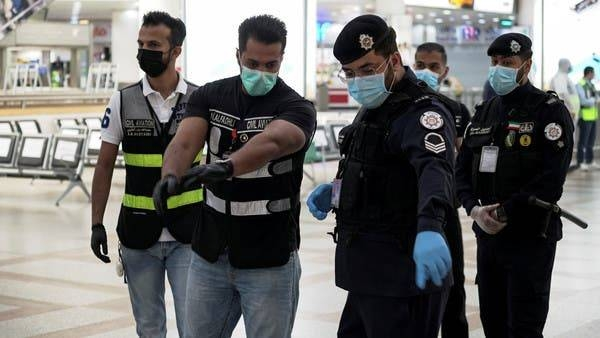 Police and civil aviation personnel wearing protective face masks are seen in Kuwait in this file picture. — Courtesy photo