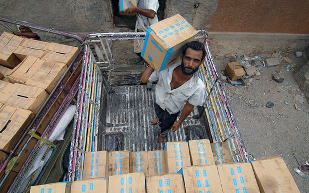 Workers stack food assistance in a warehouse in Lahj, Yemen. — courtesy WFP