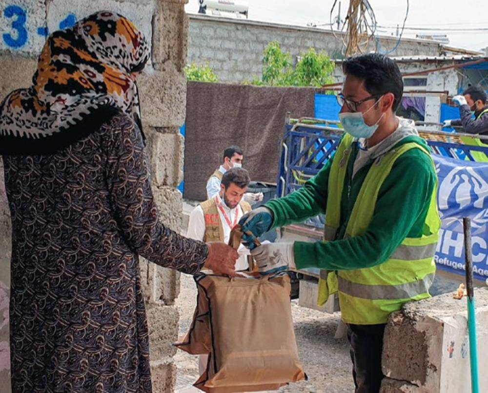 UNHCR and partner staff distribute sanitary kits to a Syrian woman, one of 13,000 refugees living at Darashakran camp in Erbil, Kurdistan Region of Iraq. — courtesy photo by UNHCR / Shaza Shekfeh
