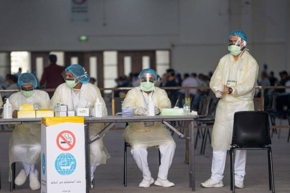 Nurses await to admit people in a makeshift coronavirus testing center at the Mishref Fair Grounds in Kuwait City in this file photo.
