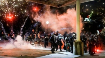 A firework explodes near a police line during a protest in Atlanta.