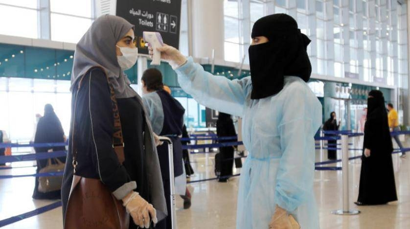 A security woman checks the temperature of a woman at Riyadh's King Khalid International Airport on Sunday. -- Courtesy photo