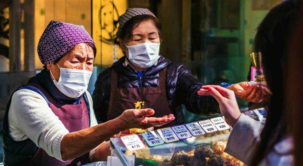 Vendors wear face masks at a food market in Japan. — courtesy Unsplash/ Jérémy Stenuit