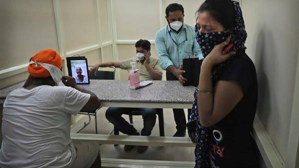 A man speaks with his mother who has been admitted in a hospital through a video phone facility by the COVID help desk, as another leaves crying after talking to her relative, outside a hospital, in New Delhi. — Courtesy photo