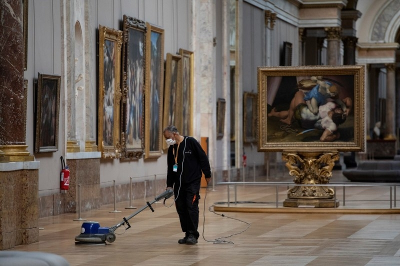 An employee cleaning the floor of a room of the Musee du Louvre in Paris. — Courtesy photo