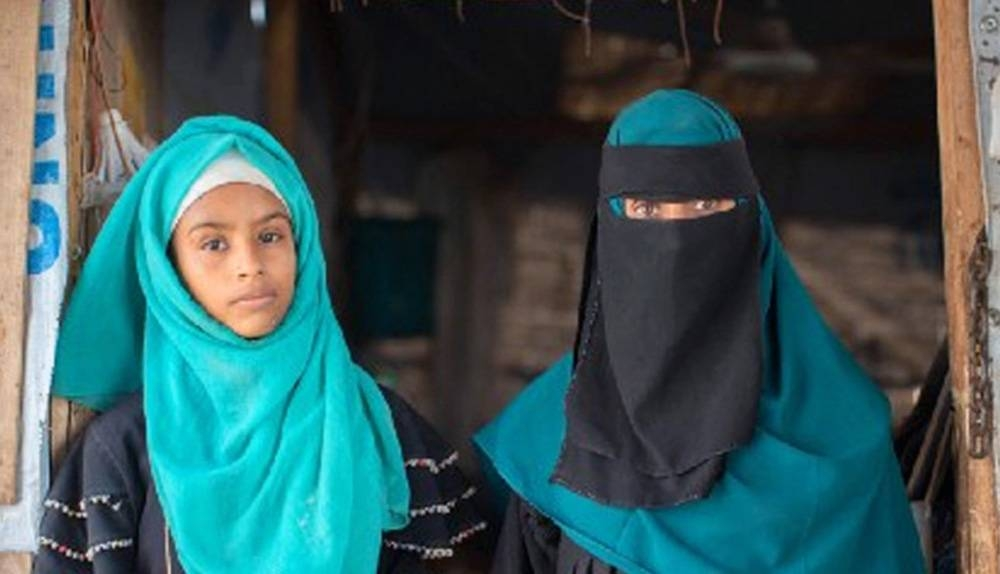 Rania and her eldest daughter, Amani, stand in the entrance to their home in a camp for internally displaced people in Lahj, Yemen. — courtesy WFP/Mohammed Awadh