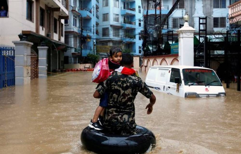 A child is being rescued by the Nepalese security personnel as heavy rains left the streets flooded.