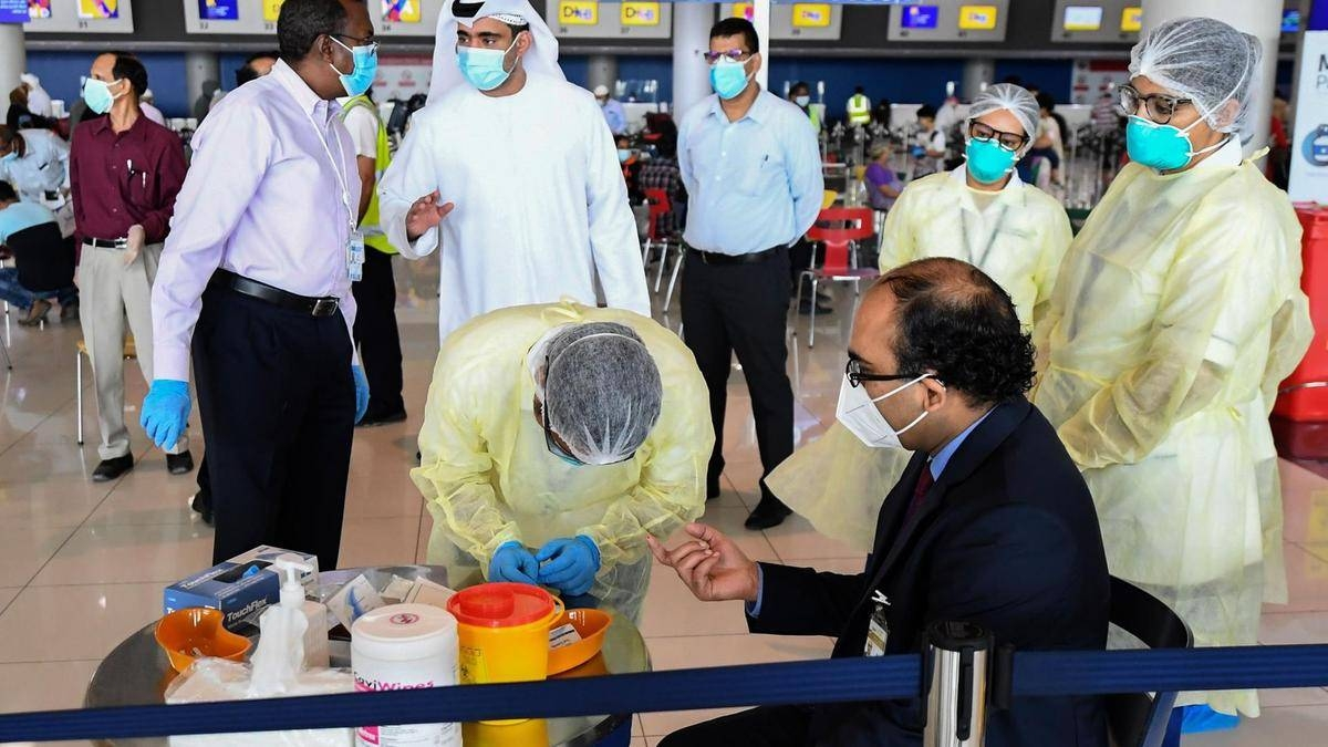 Health workers test an Indian citizen at Dubai International Airport before he boards a repatriation flight. — Courtesy photo