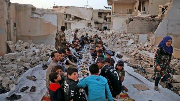 Men and children sit together in the midst of ruins to eat in Aleppo, Syria. — File photo