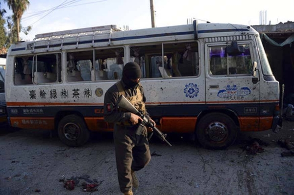 An Afghan security policeman stands guard near a damaged bus after a suicide attack in Nangarhar province east of Kabul, Afghanistan, in this file photo.