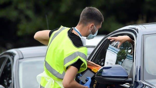 An official delivers a testing kit through a car window at a mobile drive through coronavirus testing center, in Richmond, London. — Courtesy photo