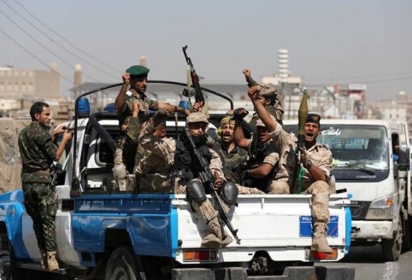 Houthi militants ride on the back of a police patrol truck after participating in a gathering in Sanaa in this file photo.