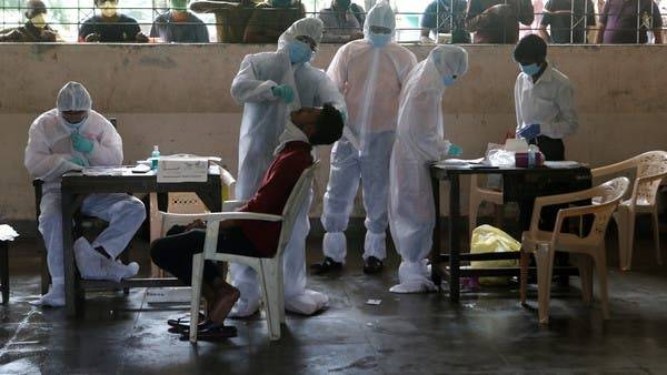 A health worker collects a swab sample from a man at a school in Mumbai. — File photo
