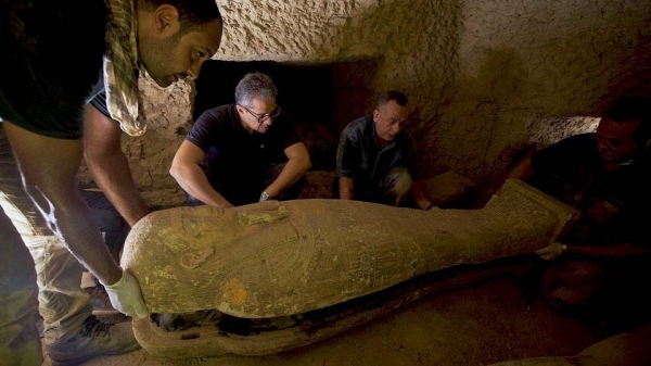 Secretary General of the Supreme Council of Antiquities Mostafa Waziri (center) inspects one of the 13 2,500 year-old wooden coffins discovered in a burial shaft at the desert necropolis of Saqqara south of Cairo. — Courtesy photo
