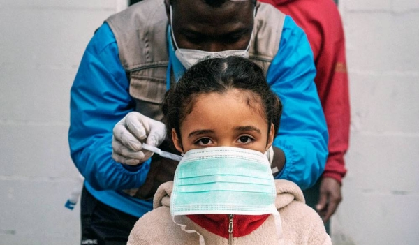 A seven-year-old girl is given a protective mask prior to a health screening in the informal settlement in Rome, Italy, where she lives. — courtesy UNICEF/Alessio Romenzi.