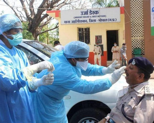 Medics examine a policeman for COVID-19 in the Indian city of Bhopal. — File photo